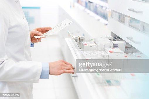Pharmacist filling prescription in pharmacy