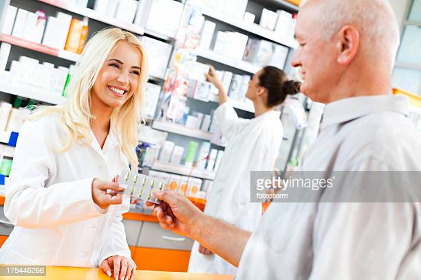 Pharmacist giving pills to a customer