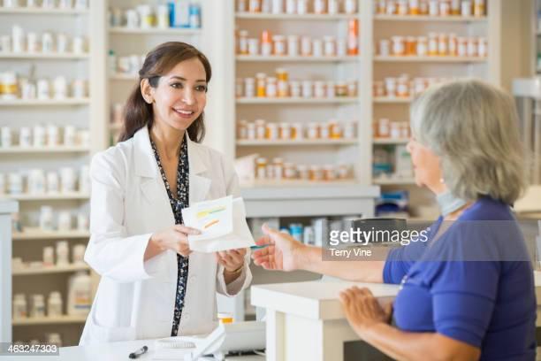 Pharmacist giving prescription to customer