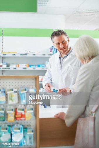Pharmacist giving senior customer advice : Stock Photo