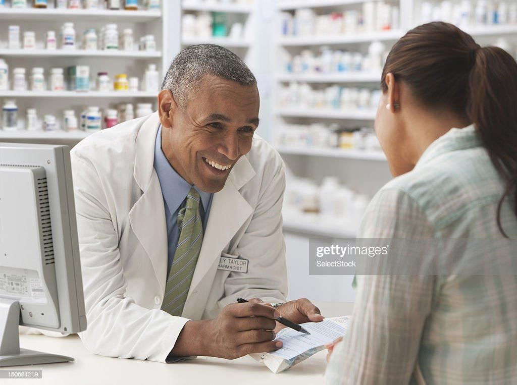 Pharmacist going over prescription with customer : Stock Photo