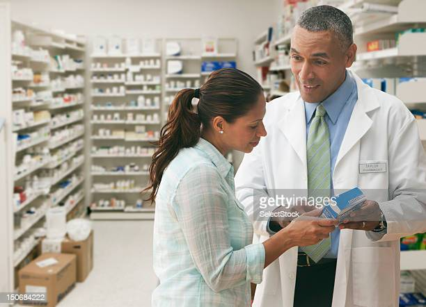 Pharmacist going over prescription with customer