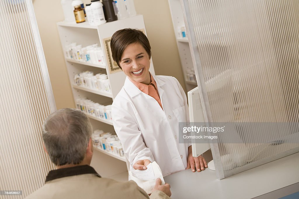 Pharmacist handing a man a prescription : Stock Photo