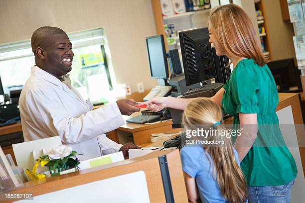 Pharmacist handing credit card back to customer