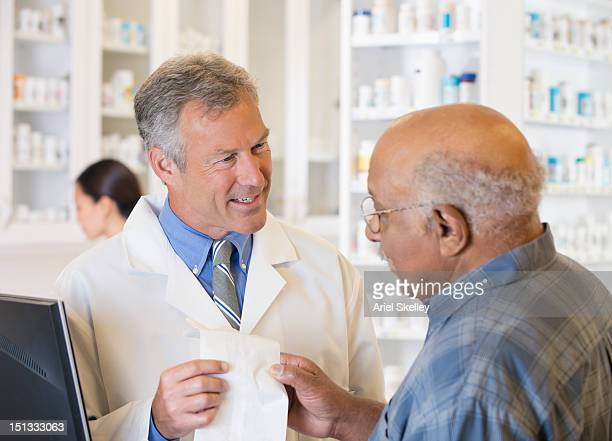 Pharmacist handing customer prescription