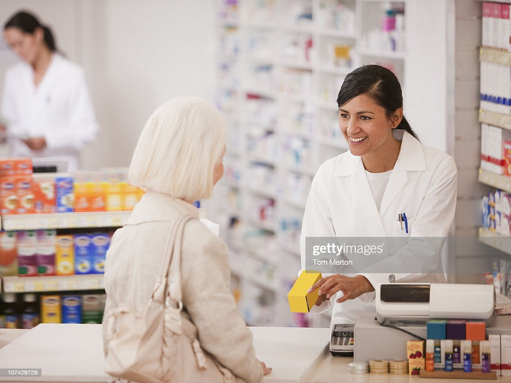 Pharmacist handing medication to customer in drug store : Stock Photo