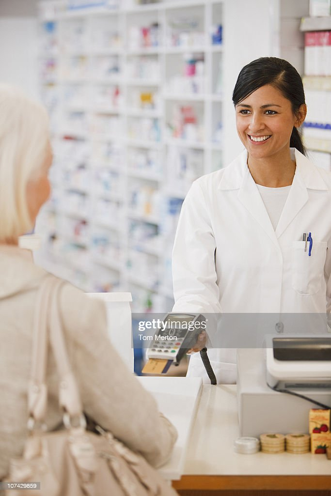 Pharmacist holding security device for customer in drug store : Stock Photo