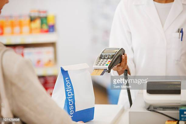 Farmacêutico segurando o dispositivo de segurança para o cliente em loja de