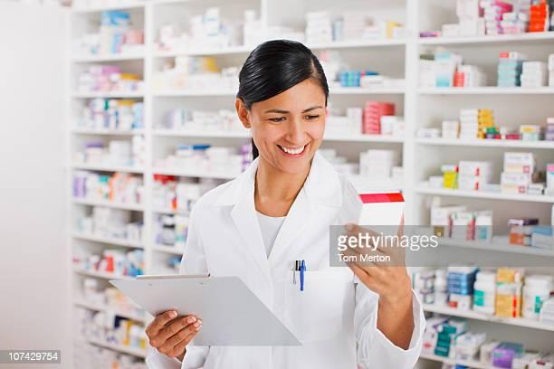 Pharmacist in drug store holding clipboard reading medication box