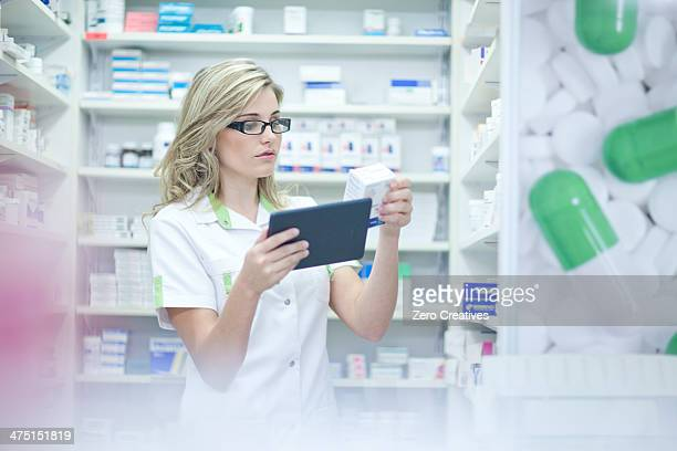 Pharmacist looking at digital tablet and medication