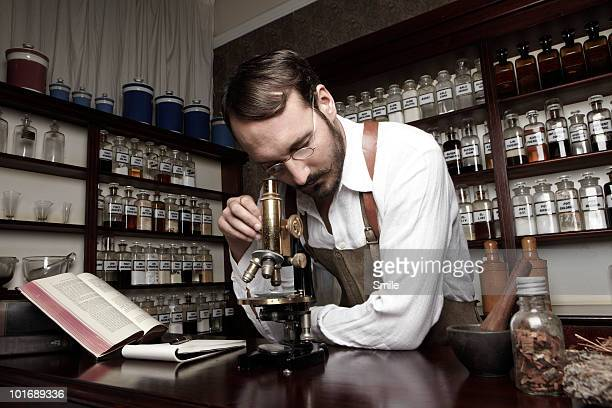 Pharmacist looking through a microscope