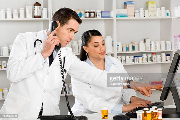 Pharmacist on computer and doctor using phone