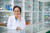 Portrait of senior Vietnamese pharmacist in drugstore