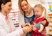 Pharmacist putting bandage on doll