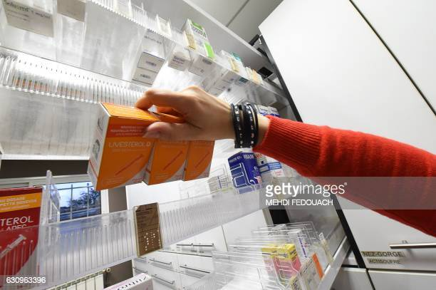 A pharmacist removes boxes of 'Uvesterol D' vitamin medication from a shelf in a pharmacy in Bordeaux southwestern France on January 4 after French...