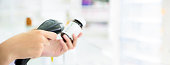 Pharmacist scanning medicine bottle with barcode scanner in pharmacy - panoramic banner with copy space on the right