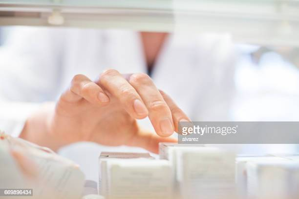 Pharmacist searching medicine in store