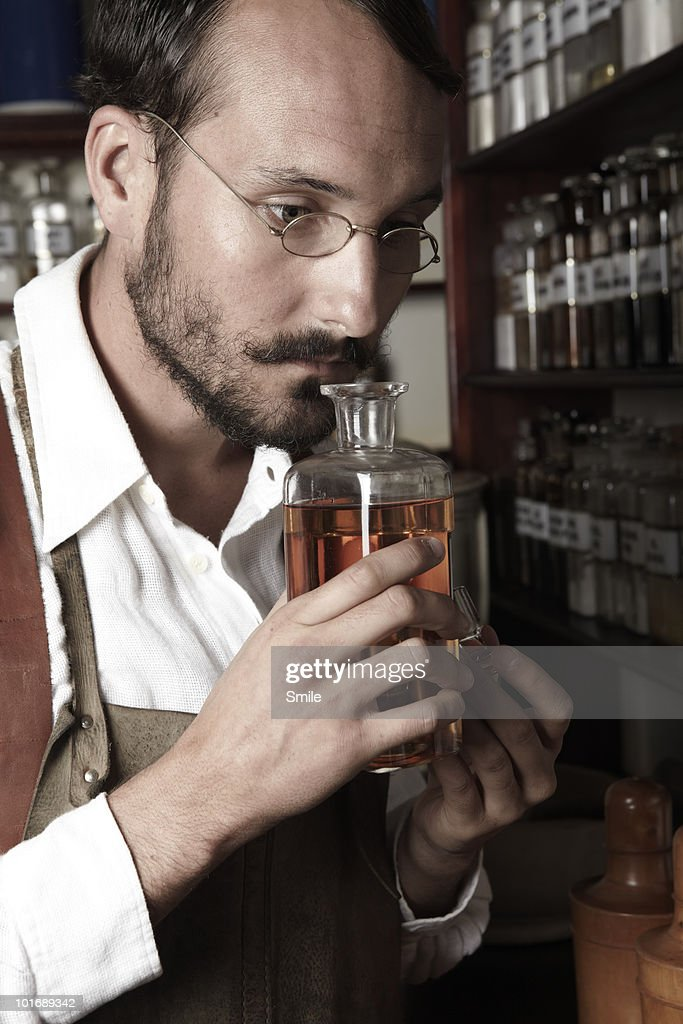 Pharmacist smelling a bottle : Stock Photo