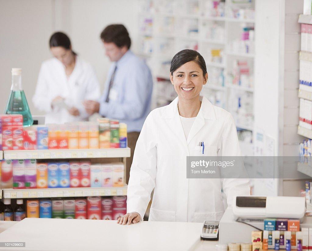 Pharmacist standing at cash register in drug store : Stock Photo