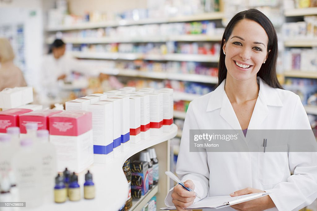 Pharmacist standing in drug store : Stock Photo