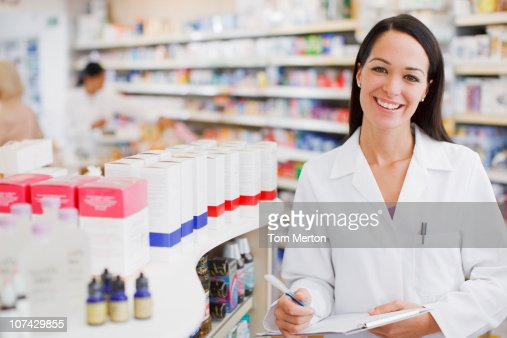 Pharmacist standing in drug store : Stock Photo
