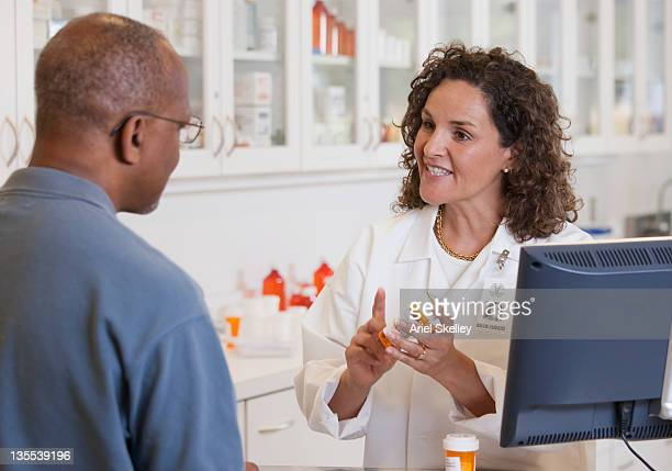 Pharmacist talking to customer about prescription
