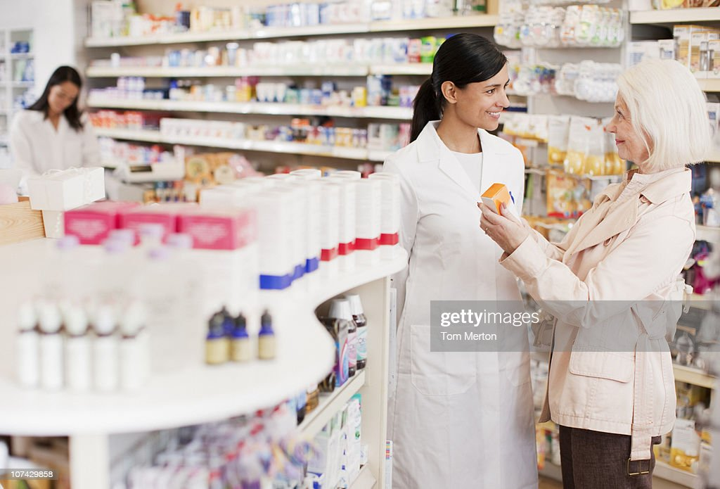 Pharmacist talking to customer in drug store : Stock Photo