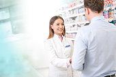 Pharmacist talking to customer in pharmacy
