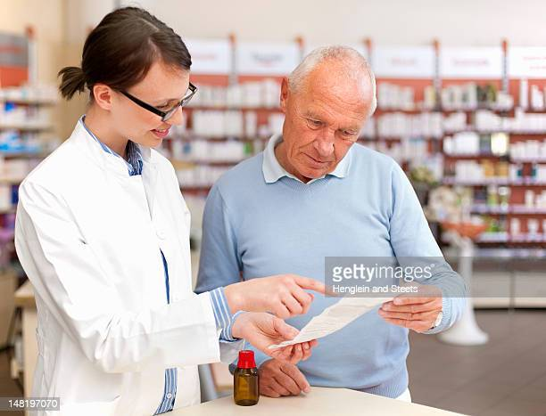 Pharmacist talking to patient in store