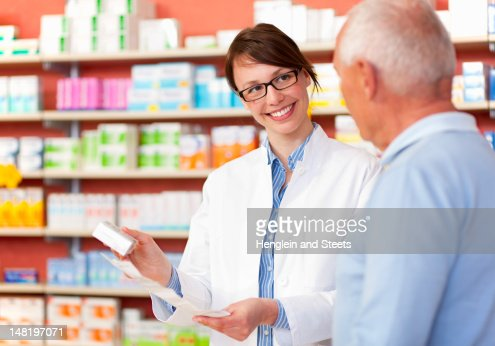 Pharmacist talking to patient in store : Stock Photo
