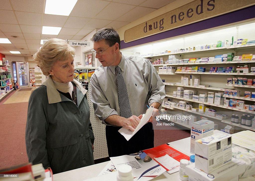 Pharmacist William Hewitt speaks with Aase KjosHansen about her options under the new Medicare prescription drug benefit program at Rosemont Pharmacy...