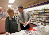 Pharmacist William Hewitt speaks with Aase KjosHansen about her options under the new Medicare prescription drug benefit program at Rosemont Pharmacy...