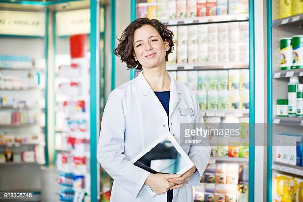 Pharmacien avec tablette numérique dans le magasin chimiste