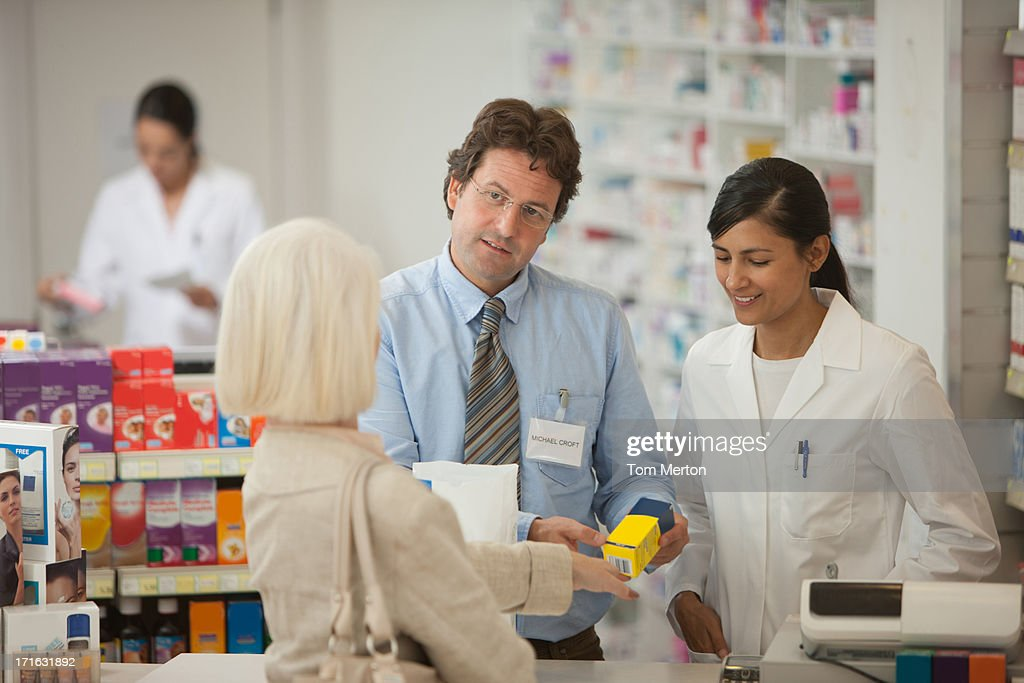Pharmacists answering questions for customer in drug store : Stock Photo