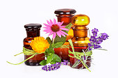 Old chemist`s bottles with lavender, calendula and echinacea for medicine and wellness.