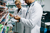 Two chemist working in pharmacy drugstore. Male and female pharmacists checking inventory at pharmacy.