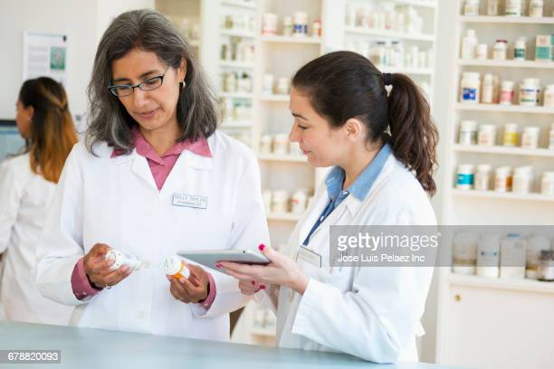 Pharmacists checking prescription with digital tablet in pharmacy