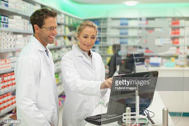 Pharmacists using computer at counter