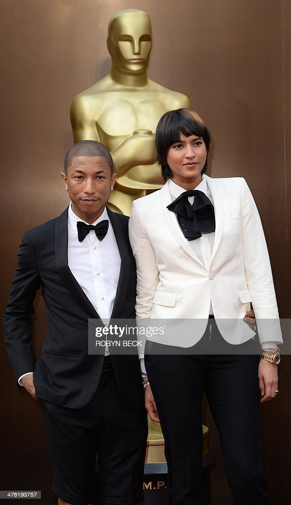 Pharrell Williams (L) and Helen Lasichanh arrive on the red carpet for the 86th Academy Awards on March 2nd, 2014 in Hollywood, California. AFP PHOTO / Robyn BECK