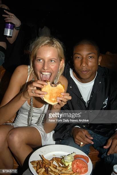 Pharrell Williams and Karolina Kurkova share a burger at a party to plug the season opening of the Hudson Hotel garden She hosted the bash