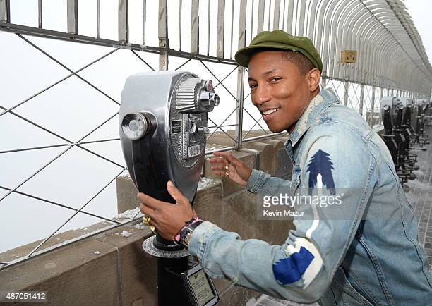 Pharrell Williams looks out from the top of the Empire State Building after lighting it yellow for International Day of Happiness at on March 20 2015...