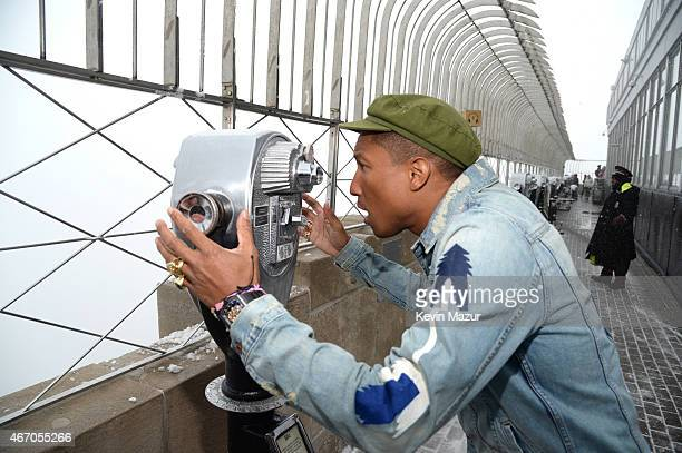 Pharrell Williams looks out from the top of the Empire State Building after lighting it yellow for International Day of Hapiness at on March 20 2015...