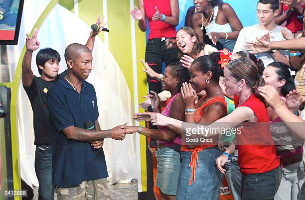 Pharrell Williams on right and Chad Hugo of The Neptunes greet fans on stage during MTV's Total Request Live at the MTV Times Square Studios August...