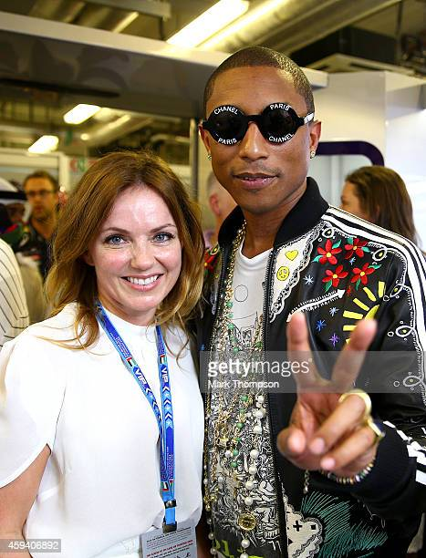 Pharrell Williams poses with Geri Halliwell in the Infiniti Red Bull Racing garage during qualifying for the Abu Dhabi Formula One Grand Prix at Yas...