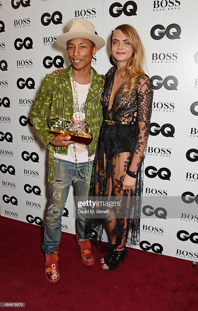 Pharrell Williams, winner of the Solo Artist award, and presenter Cara Delevingne attend the GQ Men Of The Year awards in association with Hugo Boss at The Royal Opera House on September 2, 2014 in London, England.