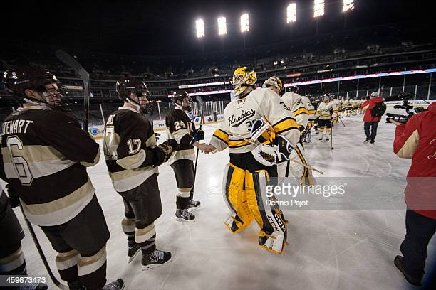 Pheonix Copley of the Michigan Tech Huskies congratulates Shane Berschbach of the Western Michigan Broncos on December 28 2013 at Comerica Park in...