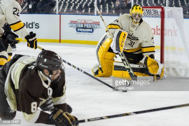 Pheonix Copley of the Michigan Tech Huskies makes a big save against Jacob Johnstone of the Western Michigan Broncos on December 28 2013 at Comerica...