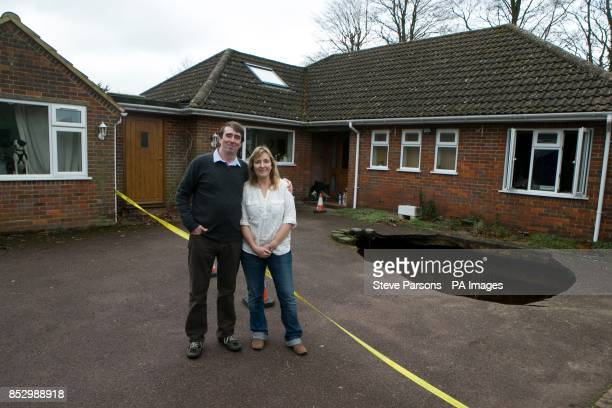 Phil and Liz Conran stand outside their home in Main Road Walter's Ash High Wycombe Buckinghamshire after a 30ftdeep sinkhole opened up in the...