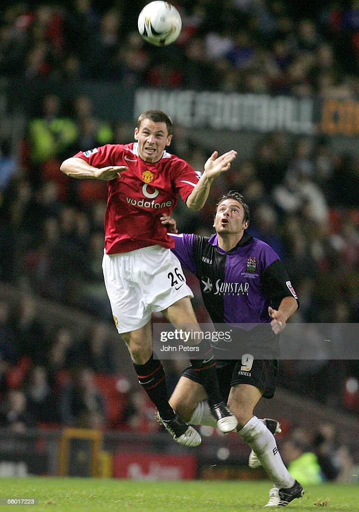 Phil Bardsley of Manchester United clashes with Giuliano Grazioli during the Carling Cup third round match between Manchester United and Barnet on...