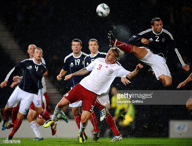 Phil Bardsley of Scotland clears the ball under pressure from Simon Kjaer of Denmark during the International Friendly Match between Scotland and...
